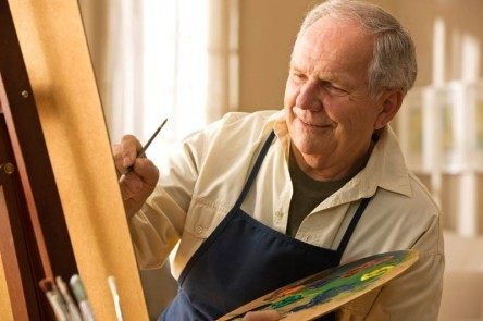 Elderly man painting on canvas