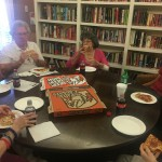 Residents and students enjoying pizza in the library.
