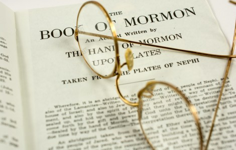 The opening page in the Book of Mormon. A pair of old glasses rests upon the page.
