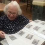 Blanche smiling at her photos.