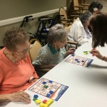 April helping a resident by showing her the picture she needed to match.