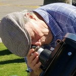 Bill Lofquist adjusting his telescope equipped with a safety lens.