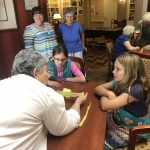 The Girl Scouts visit with residents and assist in cutting bags into strips.